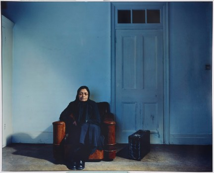 A woman with black turban sitting on sofa in room with blue wall