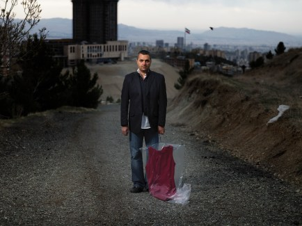man standing in the middle of a gravel road holding a burgundy dress in a plastic garment bag