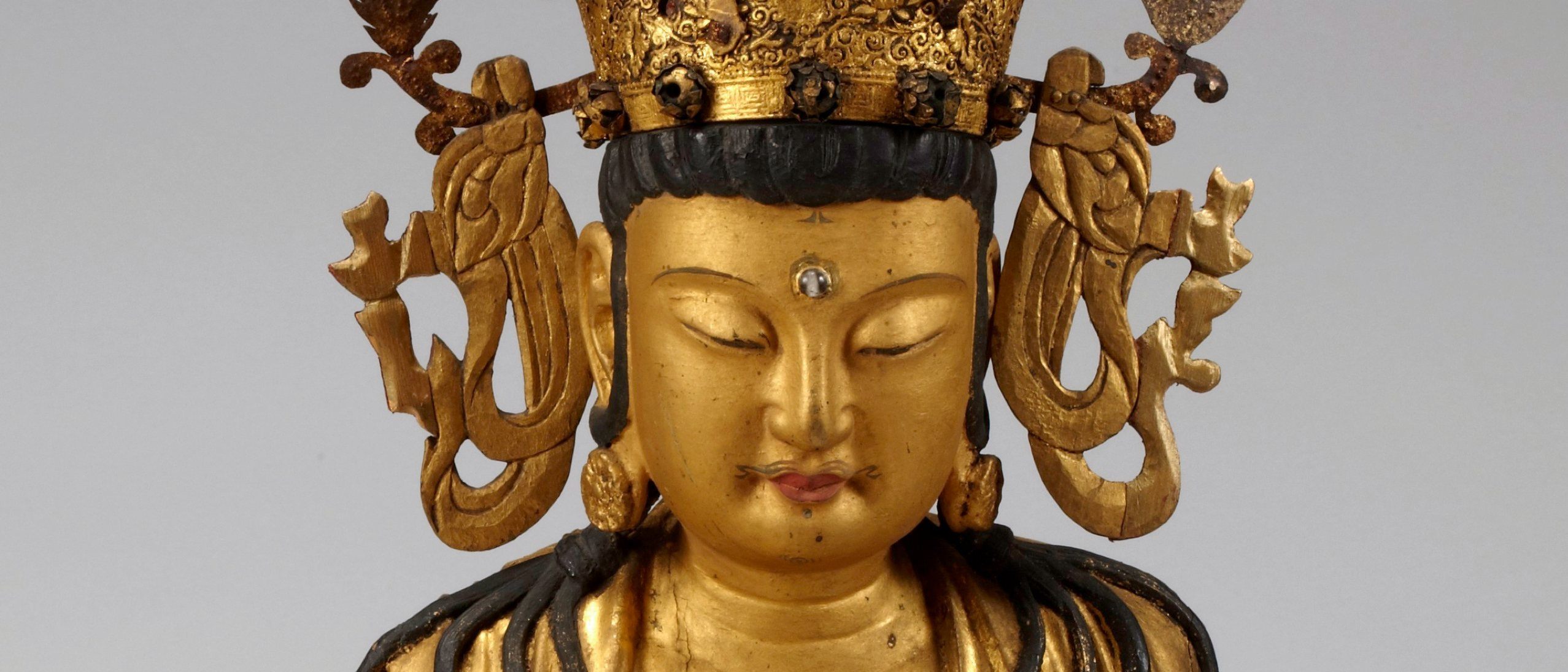 gilt statue of a Bodhisattva in a large headress