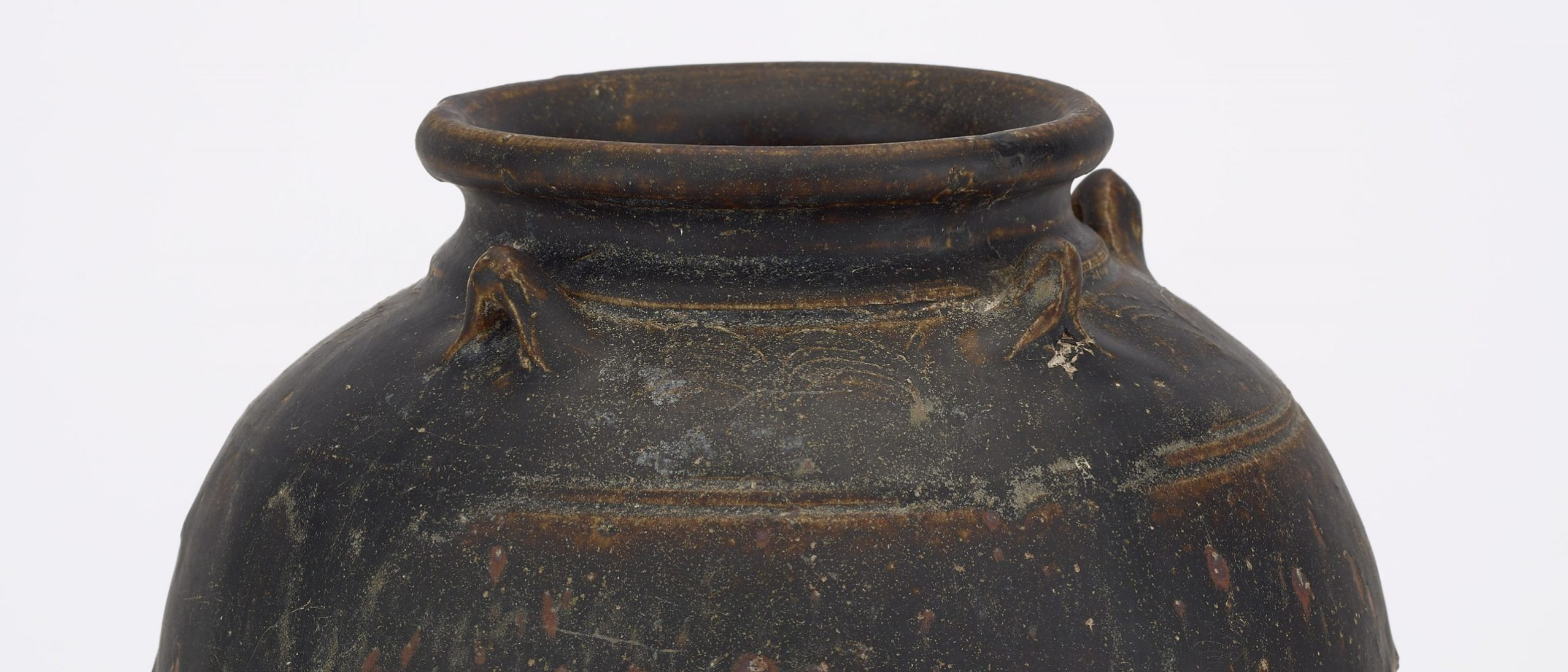detail from jar with four lugs. the mouth of a rounded brown jug with three lugs visible