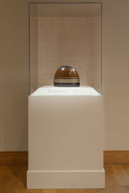 A hemispherical vase with bands of dark brown, gold and copper colored metal sits in a tall rectangular case