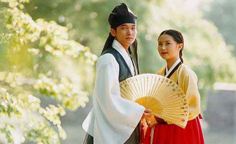 A man and woman standing close together looking into the distance in the foreground. The man holds an open fan at the waist.