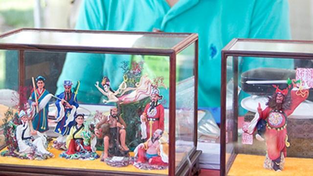photo of a man with small figures in a glass box
