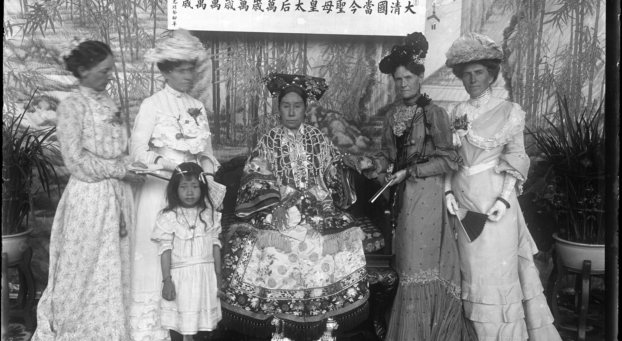a woman sitting surrounded by 4 other women standing