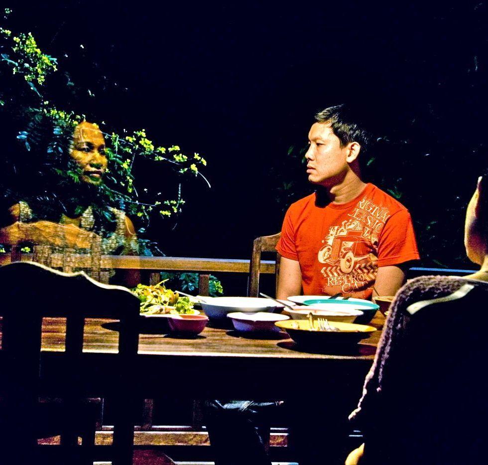 "A still image from the Thai film ""Uncle Boonmee"". There are three figures seated at a dining table set with food. One diner faces away from the viewer. The other diner is a man with dark hair in an orange and yellow tee shirt. He is facing the third figure, at left, a ghostly apparition of a woman."