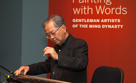 photo of a man using a zither in front of a red wall