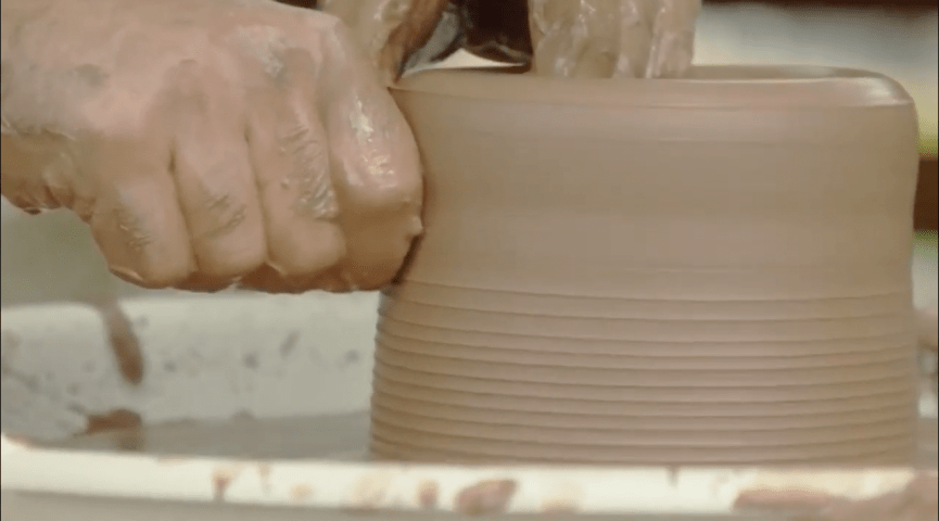 photo of a hand forming a bowl out of clay
