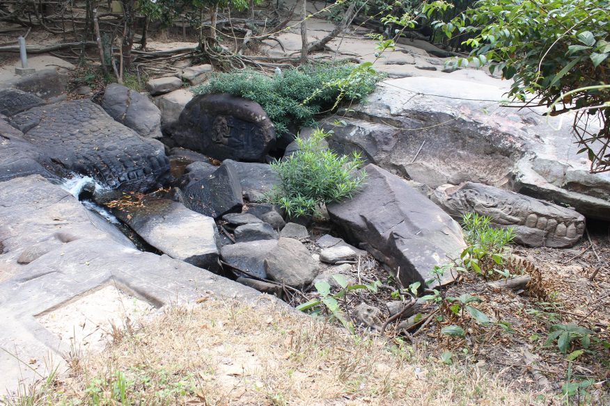 Quarry area in jungle with two carvings of Vishnu reclining and lingas
