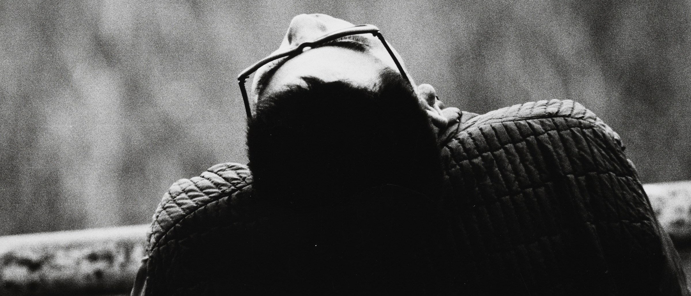 detail, Ueno Park, Tokyo, from the series, Cries, at Ueno Park, by Suda Issei. Black and white photo of a person seen from behind, wearing glasses and a textured top, leaning back so the top of their head and part of the face can be seen.