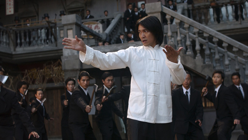film still from Kung Fu Hustle showing a man braced to take on a number of people with axes around him