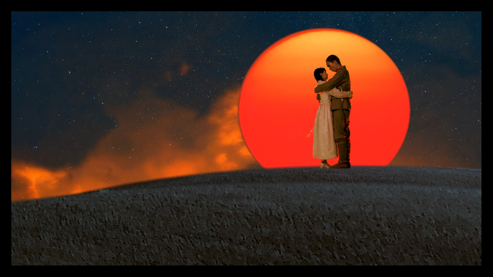 A couple standing on a hilltop and embracing, they are silhouetted in front of an orange sun rising or setting.