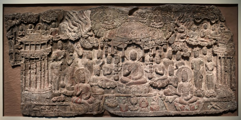High relief carving of Western Paradise. Amitabha presides over a lotus pond that contains flowers opening to reveal newborn souls. Numerous deities and celestial attendants fill in the tableau.