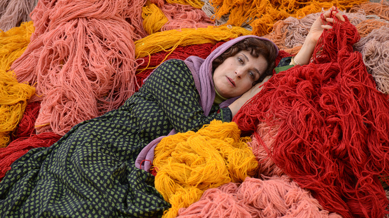 detail from a still from African violet, courtesy of Venera Films, showing a woman lying among piles of multicolored wool