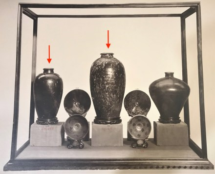 Black and white photograph of a case from the 1914 exhibition. Arrows point to some of the Chinese ceramics from Freer's collection.