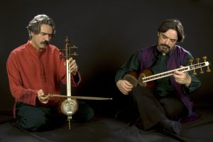 Two musicians, seated on floor, playing kamanchech and tar, eyes closed in concentration.