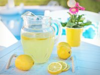 A pitcher of lemonade on a tray surrounded by whole and sliced lemons on a poolside table