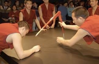 Monks in red use a large protractor to create guides on the table.