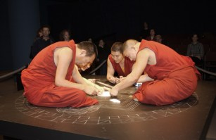 Four monks in red begin adding white sand to the center of the mandala. Two stand, leaning far over the table, while two more sit cross-legged on top of the table.