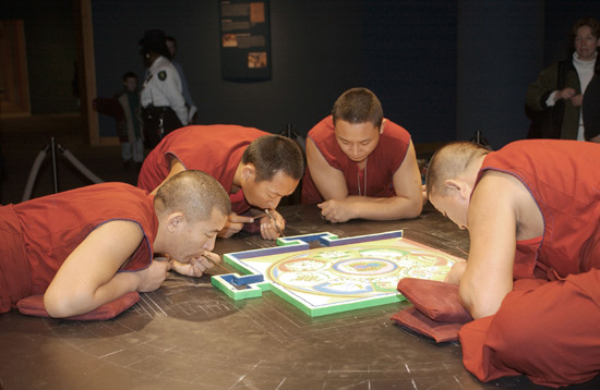 Four monks in red lean in close to the mandala. The center is already intricately drawn. They very steadily place sand upon a raised boarder surrounding the center of the mandala. One is seated on the table.