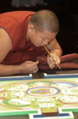 A single monk in red leans in close to the mandala, with cushions under his forearms to steady him.