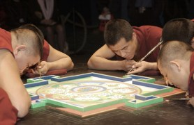 Close-up of five monks working on the mandala.