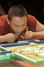 A monk in red concentrates as he adds sand to the mandala.