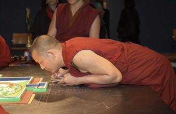A monk leans over and rests his upper body on the table to steady himself and lean in close to the mandala.