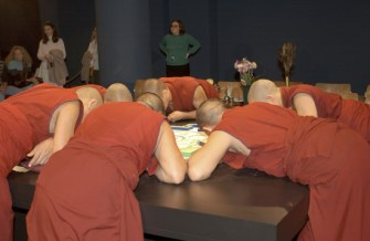 Several monks in red, all leaning over the table, heads down as they work on the mandala.