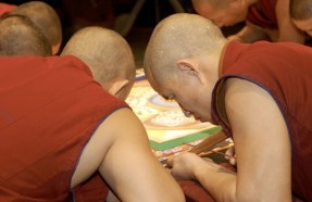Monks lean in close, heads down as they work on the edge of the mandala.