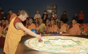 A young monk wearing gold and red robes creates the first brush-stroke to begin destroying the mandala.
