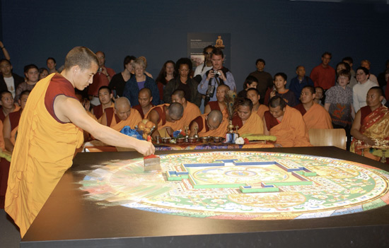 A young monk wearing gold and red robes continues drawing the brush through the mandala, destoying the image and blending the colors of a portion of the mandala.