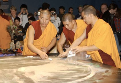 Monks collect the sand of the destroyed mandala in a Ziploc bag.