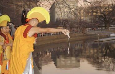 A monk in red and gold robes and a yellow crested headdress pours sand from the mandala into the Tidal Basin.