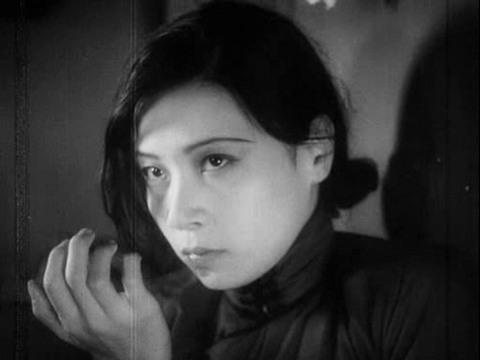 Close up of Ruan Lingyu in the black and white silent film The Goddess, her hand is curled near her face and she stares off screen