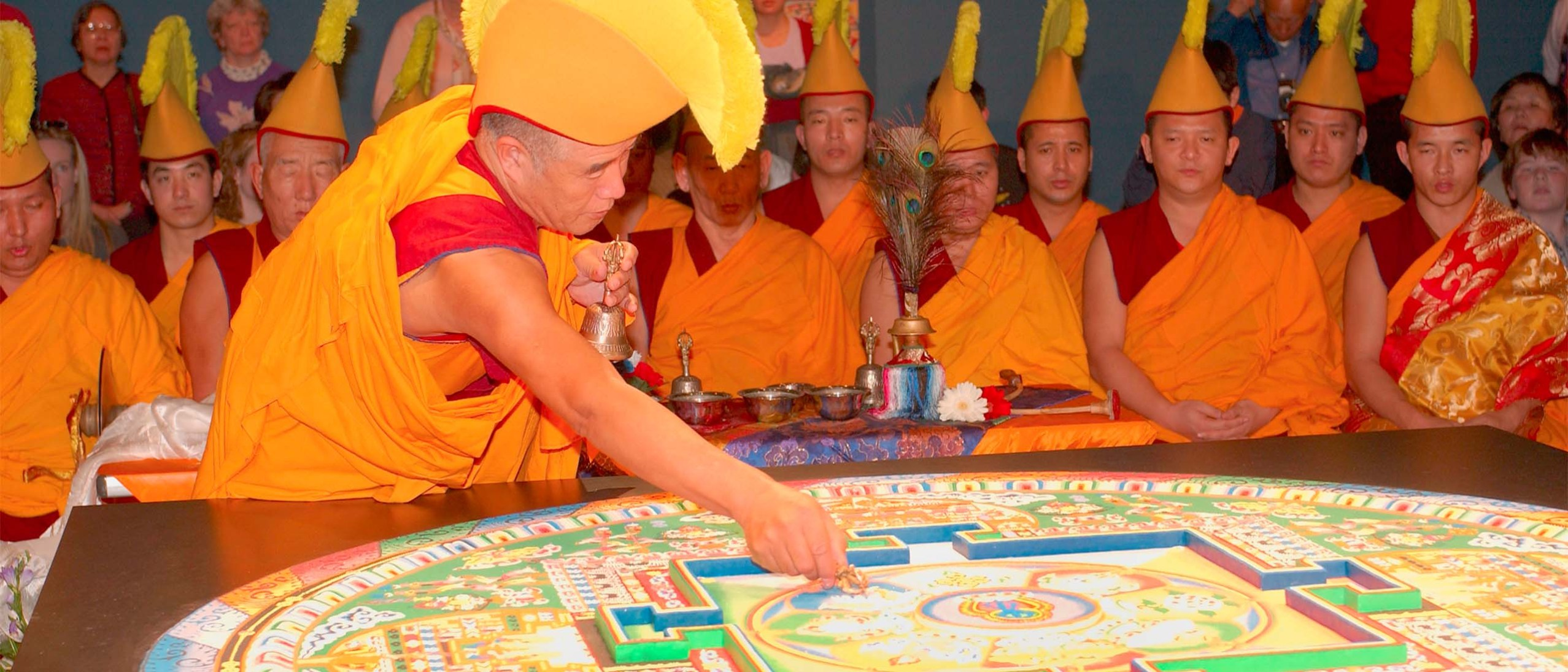 A monk in red and gold robes, wearing a yellow crested headdress leans over the finished mandala, holding a bell. Monks wearing the same clothes are seated in meditation behind him.