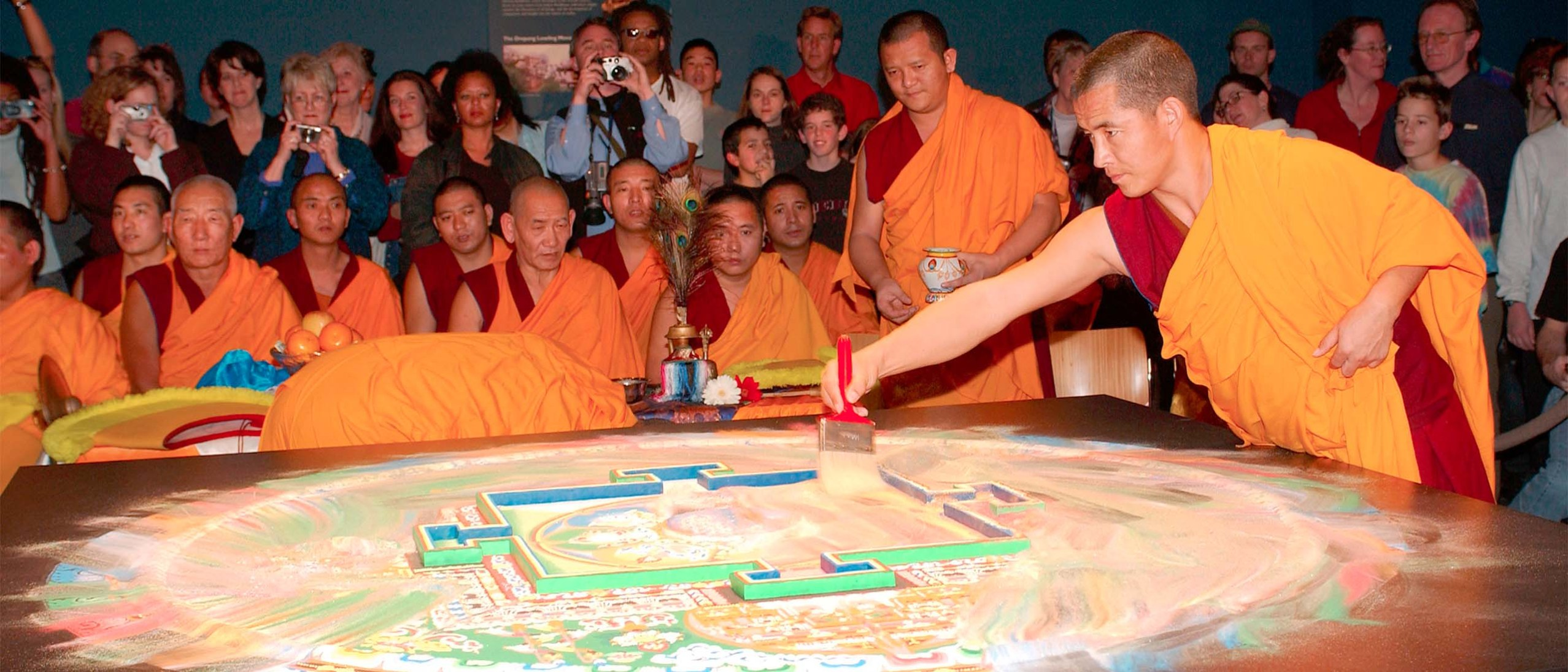 A young monk wearing gold and red robes continues drawing the brush through the mandala, destoying the image and blending the colors of the mandala, now almost completely destroyed.