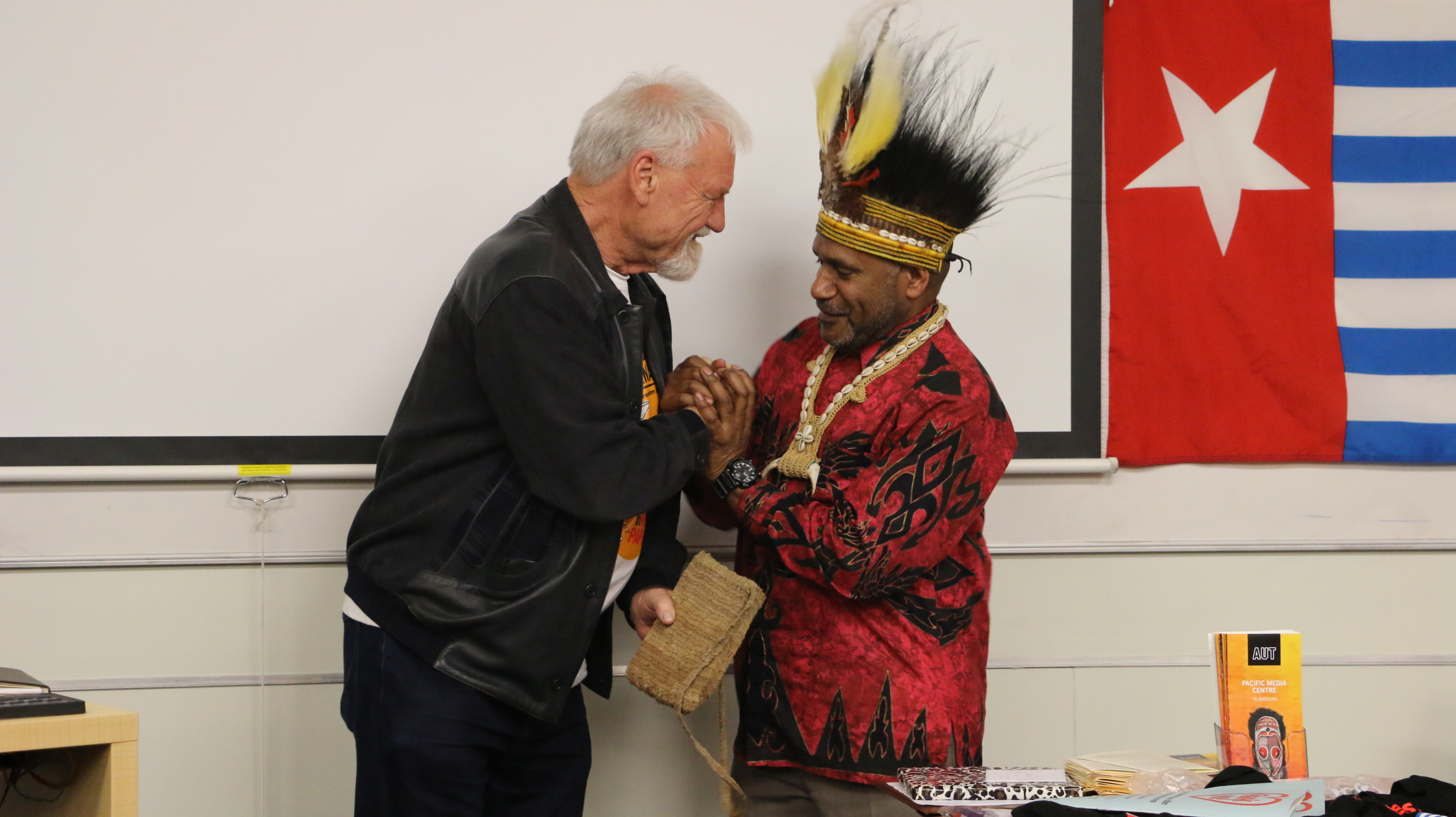 """Free West Papua advocate Benny Wenda presents Pacific Media Centre Professor David Robie with a traditional """"bilum"""" for his journalism about West Papuan freedom. Image: Kendall Hutt/PMC"""