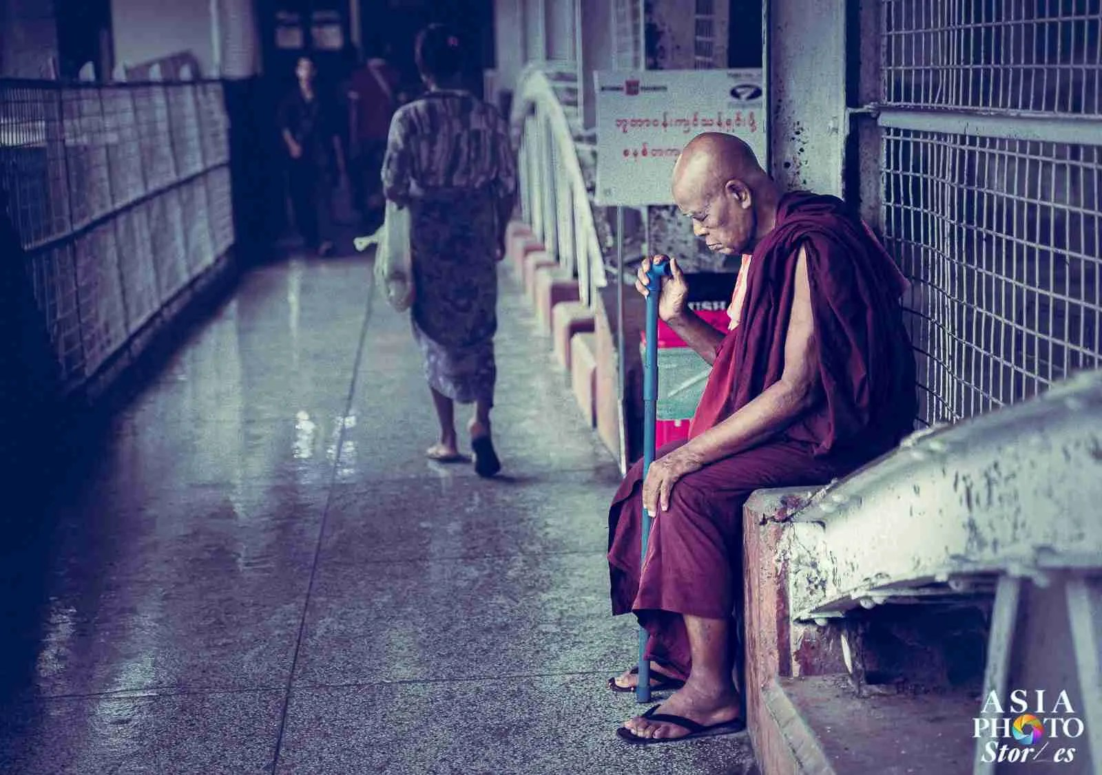 A monk takes refuge in an open-windowed corridor during a blustery thunderstorm at Yangon's Central Railway Station.