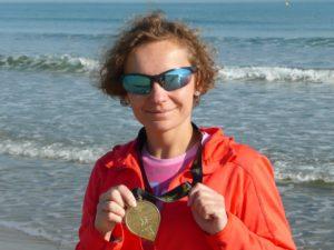 Dziewczyna z medalem maratonu w Walencji na tle morza