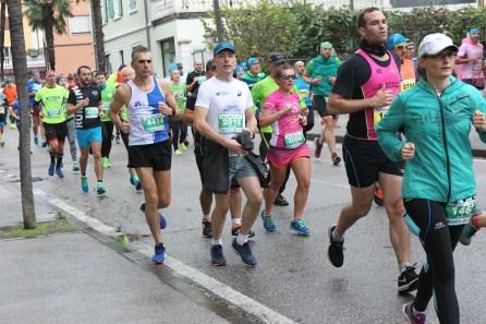 Biegacze i bieganie wzdłuż rzeki. Na trasie półmaratonu Garda, Włochy