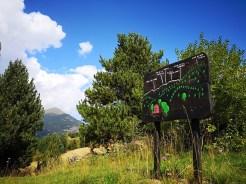 Drewniana tablica z oznakowanymi szlakami i nazwami szczytów w oddali, Pireneje w Andorze