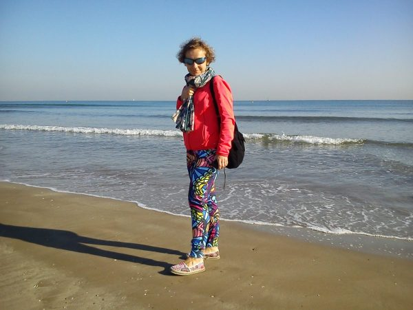 Kobieta w kolorowych sportowych ubraniach na tle morza