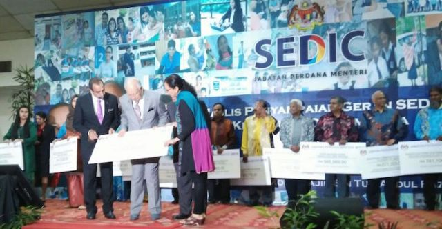 SWAN president Satwant Kaur receiving the mock cheque at the SEDIC event in Kuala Lumpur on 5 Nov 2015. Also on stage is SEDIC director Prof Dr N.S Rajendran.