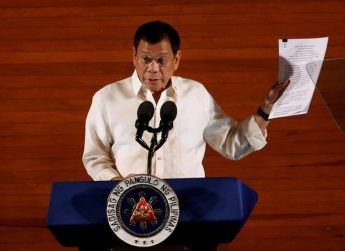 Philippine President Rodrigo Duterte holds up a copy of his speech as he speaks before the lawmakers during his first State of the Nation Address at the Philippine Congress in Quezon city, Metro Manila