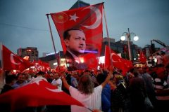 A supporter holds a flag depicting Turkish President Erdogan during a pro-government rally  in Ankara. Photo: Reuters, Baz Ratner