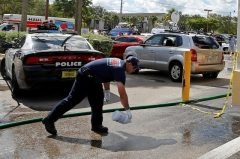 Fort Myers firefighters wash stains with bleach and a firehose in the parking lot of Club Blu after a shooting in Fort Myers