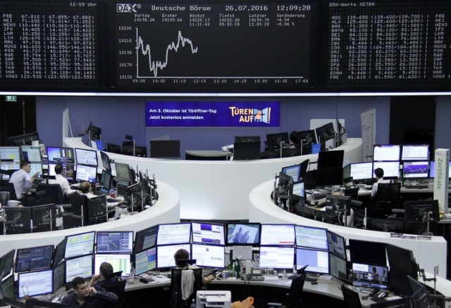 Traders work at their desks in front of the German share price index, DAX board, at the stock exchange in Frankfurt, Germany. PhotoStaff/Remote