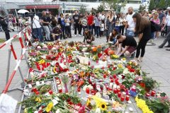 People lay flowers in front of Olympia shopping mall in Munich