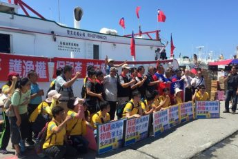 Supporters pose for photos with Taiwanese fishermen before setting sail to Itu Aba, which Taiwan calls Taiping, in protest against a tribunal's ruling on the South China Sea, in Pingtung, Taiwan