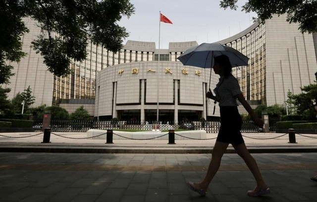 A woman walks past the headquarters of the People's Bank of China in Beijing, June 21, 2013.   Photo: Reuters/Jason Lee